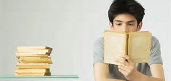 Young man reading a book at a desk. Stack of books on desk.